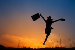 Happy Woman holding shopping bags jumping in sunset silhouette Stock Photo