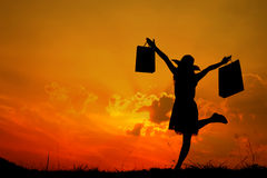 Happy Woman holding shopping bags jumping in sunset silhouette Stock Image