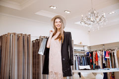 Happy woman holding shopping bags and standing in clothing store Royalty Free Stock Photos