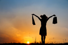 Happy Woman holding shopping bags standing in sunset silhouette Stock Photos