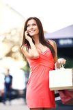 Happy woman holding shopping bags and using phone Royalty Free Stock Images