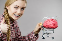 Woman holding shopping cart with brain Stock Images