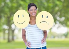 Happy woman holding smiley and sad face Royalty Free Stock Photo