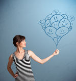 Happy woman holding smiling balloons drawing Royalty Free Stock Photography