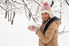 Happy woman holding snow in her hands Stock Photo