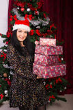 Happy woman holding stack of Christmas gifts Royalty Free Stock Photo