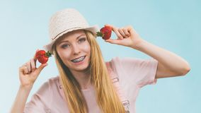 Happy woman holding strawberries. Happy cheerful teenage young woman ready for summer wearing pink outfit and sun hat holding sweet fruit red strawberries Royalty Free Stock Photography