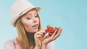 Happy woman holding strawberries. Happy cheerful teenage young woman ready for summer wearing pink outfit and sun hat holding sweet fruit red strawberries Royalty Free Stock Image