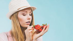 Happy woman holding strawberries. Happy cheerful teenage young woman ready for summer wearing pink outfit and sun hat holding sweet fruit red strawberries Stock Photos
