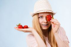 Happy woman holding strawberries. Happy cheerful teenage young woman ready for summer wearing pink outfit and sun hat holding sweet fruit red strawberries Royalty Free Stock Photo