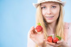 Happy woman holding strawberries. Happy cheerful teenage young woman ready for summer wearing pink outfit and sun hat holding sweet fruit red strawberries Stock Photography