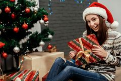 Happy woman holding surprised christmas present box. girl in swe Stock Photography