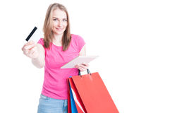 Happy woman holding tablet with shopping bags offering debit car Stock Images