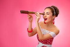 Happy Woman Holding Telescope. Pin-Up Retro style. Woman is looking through a telescope and making a surprised expression. She is standing against a pink Stock Photos
