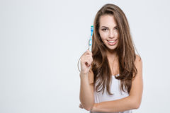 Happy woman holding toothbrush. Portrait of a happy cute woman holding toothbrush isolated on a white background and looking at camera Royalty Free Stock Photography