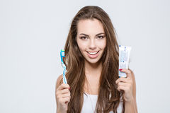 Happy woman holding toothbrush and toothpaste. Portrait of a happy woman holding toothbrush and toothpaste isolated on a white background and looking at camera Royalty Free Stock Photos