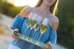 Happy woman holding tray with champagne sparkling wine into glasses outdoors at a beach. Sunset beach party royalty free stock photography