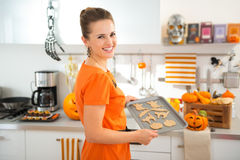 Happy woman holding tray of uncooked Halloween biscuits Stock Photos
