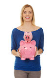 Happy woman holding two piggybanks. Royalty Free Stock Image