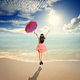 Happy Woman holding umbrella and Jumping in Sea sun sky Royalty Free Stock Photos