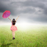 Happy Woman holding umbrella in rice fields and rainclouds Royalty Free Stock Images