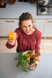 Happy woman holding up apple while holding fall vegetables Stock Photography