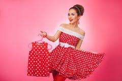 Happy Woman Holding Up Kidswear. Pin-Up Retro Stock Image