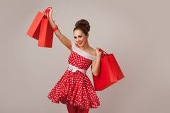 Happy Woman Holding Up Shopping Bags. Pin-up Royalty Free Stock Image