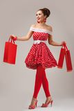 Happy Woman Holding Up Shopping Bags. Pin-up Stock Photo