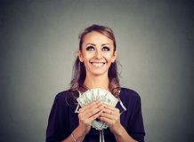 Happy woman holding US dollar bills looking up daydreaming how to spend. Happy woman holding US dollar bills over gray background and looking up daydreaming how Stock Photo