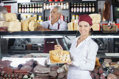Happy Woman Holding Various Cheese On Board In Store. Portrait of happy young women holding various cheese on cutting board with colleague in background at store Royalty Free Stock Photo