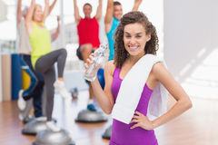 Happy woman holding water bottle in gym Stock Photo