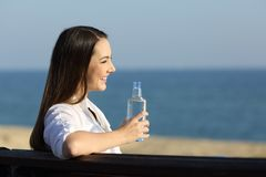 Happy woman holding a water bottle looking at horizon. On the beach Royalty Free Stock Photography