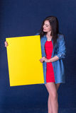 Happy woman holding a yellow blank sheet of paper Royalty Free Stock Image