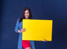 Happy woman holding a yellow blank sheet of paper Royalty Free Stock Photos