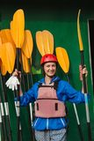 Happy woman holding yellow paddle before rafting Royalty Free Stock Photo