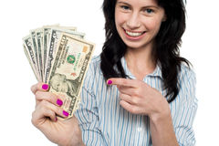 Happy woman holdng and pointing towards dollar notes stock photo