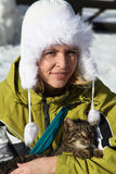 Happy woman holds a cat in winter weather, concept of friendship Stock Photography