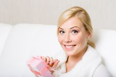 Happy woman holds a gift with pink ribbon Stock Photo