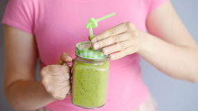 A happy woman holds a green smoothie in her hands stock video