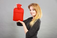 Happy woman holds hot water bottle stock photo