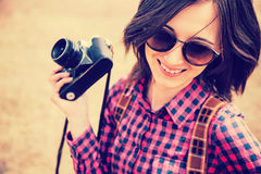Happy woman holds photo camera. Happy young woman in sunglasses holds retro photo camera Stock Photo