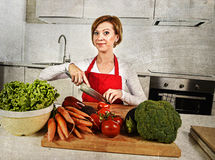 Happy woman at home kitchen preparing vegetable salad with lettu Stock Image