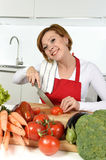 Happy woman at home kitchen preparing vegetable salad with lettuce, carrots and slicing tomato smiling Stock Photo