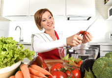 Happy woman at home kitchen preparing vegetable salad with lettuce, carrots and slicing tomato smiling Royalty Free Stock Photography