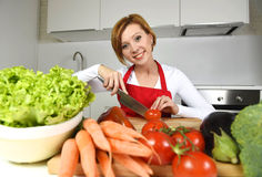 Happy woman at home kitchen preparing vegetable salad with lettuce carrots and slicing tomato Stock Photo