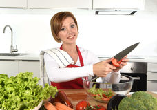 Happy woman at home kitchen preparing vegetable salad with lettuce carrots and slicing tomato Royalty Free Stock Images