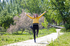 Happy woman hopping in the park celebrating. Her happiness Royalty Free Stock Photos