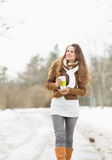 Happy woman with hot beverage walking in park Stock Photography