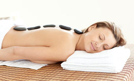 Happy woman with hot stones on her back Royalty Free Stock Photography